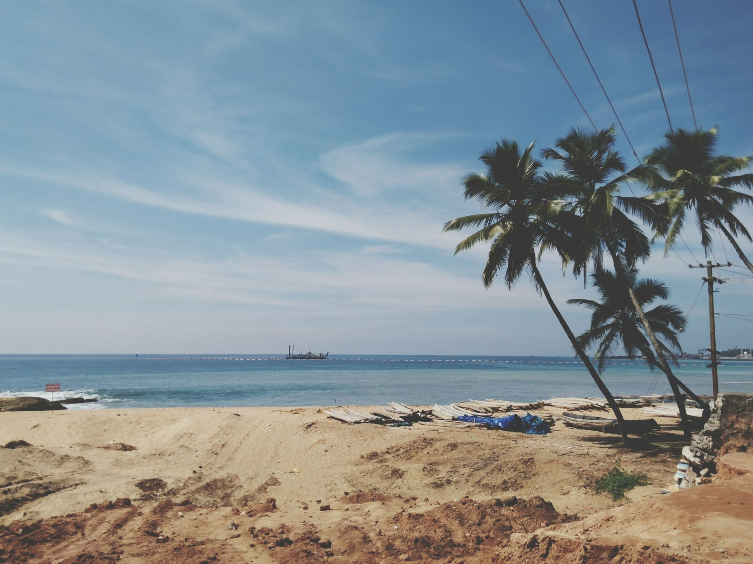 sea, beach, water, horizon over water, sky, shore, tranquility, tranquil scene, scenics, sand, beauty in nature, tree, nature, palm tree, nautical vessel, cloud - sky, transportation, idyllic, coastline, day