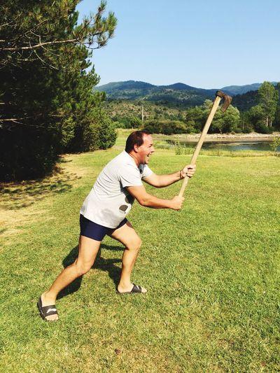 Man holding axe on grass