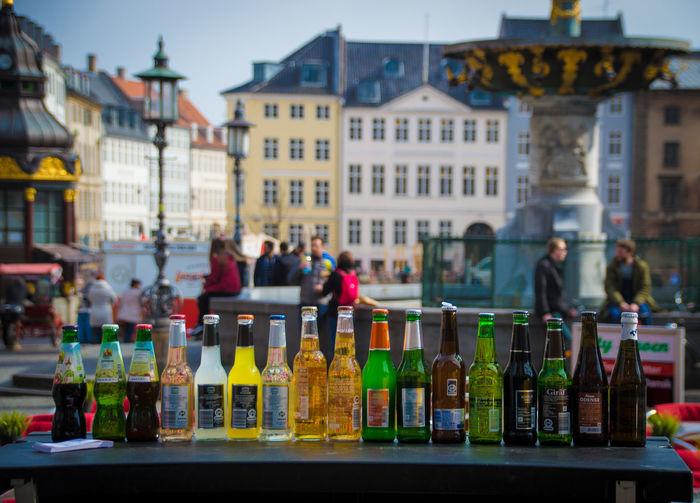 Bottles Arranged On Table Against Buildings In City