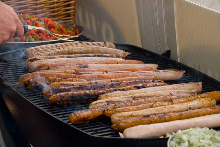 Cropped Image Of Hand Grilling Sausages On Barbecue