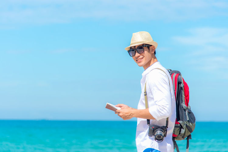 Young man wearing sunglasses standing against sea