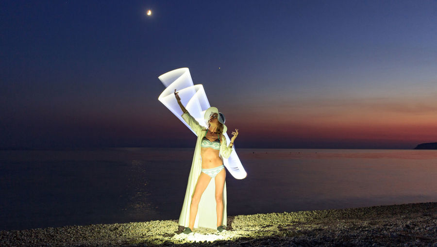 Woman Standing With Light Painting At Beach Against Sky