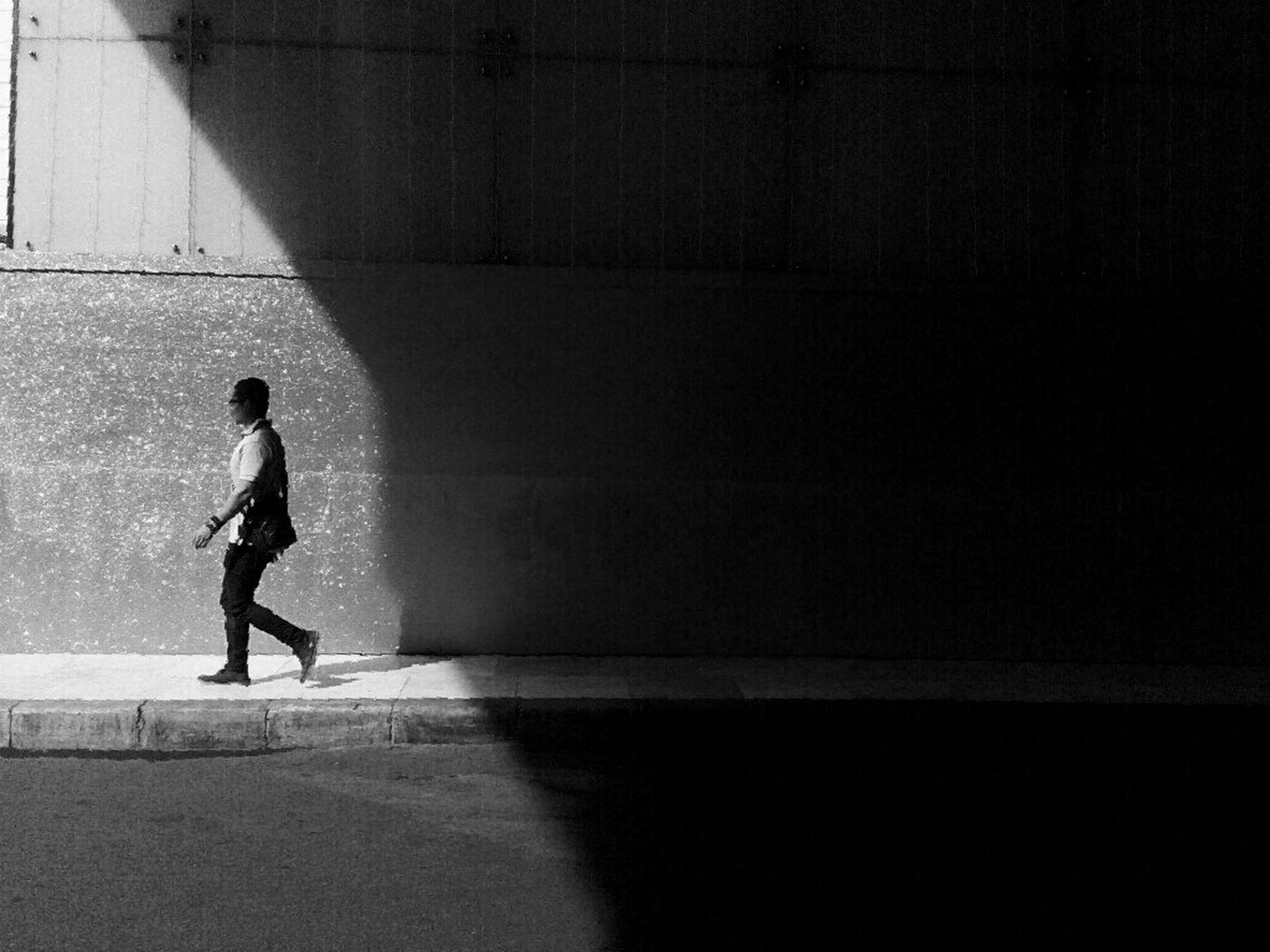 full length, lifestyles, leisure activity, walking, standing, wall - building feature, side view, casual clothing, architecture, built structure, men, shadow, rear view, wall, person, sunlight, young adult, silhouette