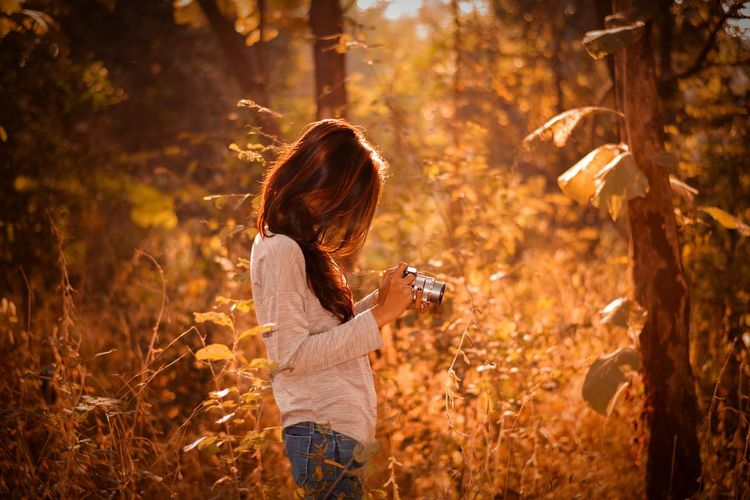 Side view of woman photographing through camera while standing at forest