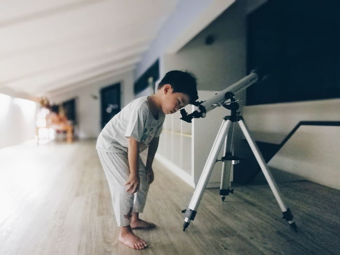 Full Length Of Boy Looking Through Telescope At Home