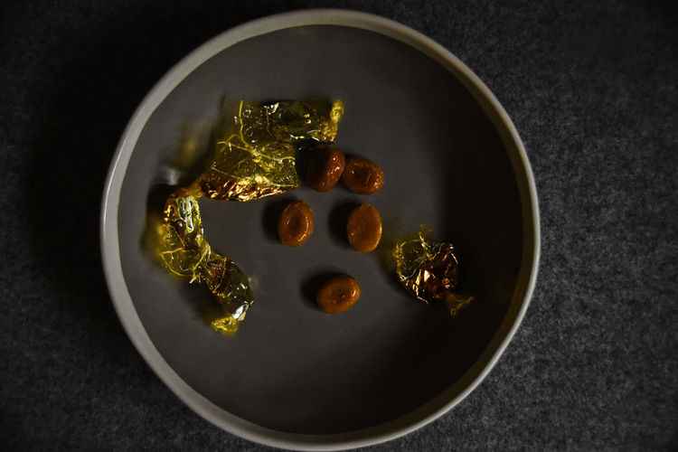 Dark Gold Unwrapped Art Bowl Calories Candies Caramel Close-up Dark Food Photography Darkness And Light Day Food Food And Drink Freshness High Angle View Indoors  No People Plate Ready-to-eat Still Life Sweet Food Table Unhealthy Eating Wherters Original
