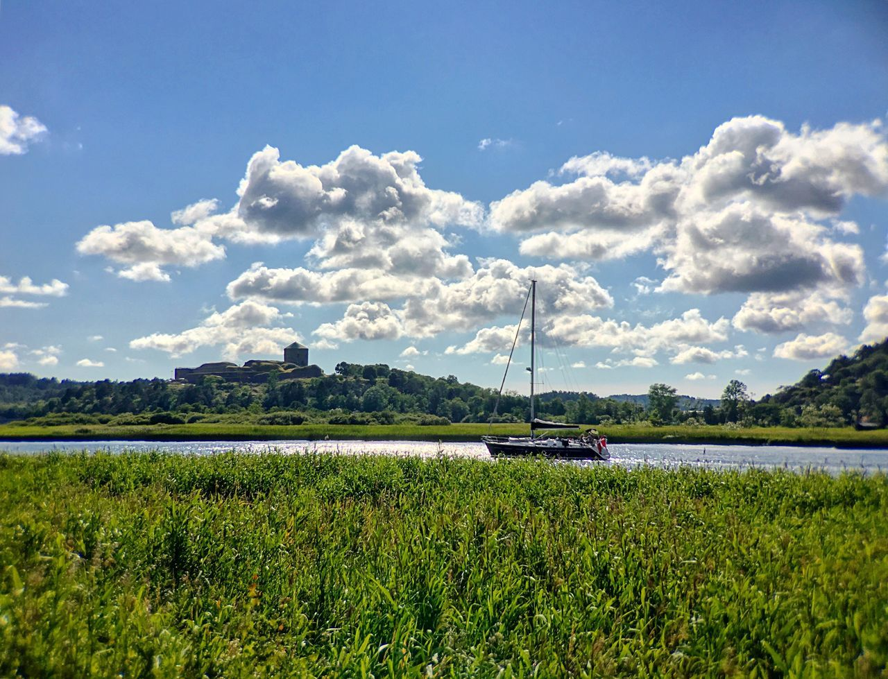 sky, field, grass, cloud - sky, nature, mode of transport, nautical vessel, tranquility, tranquil scene, beauty in nature, transportation, scenics, green color, day, outdoors, growth, no people, water, landscape, tree