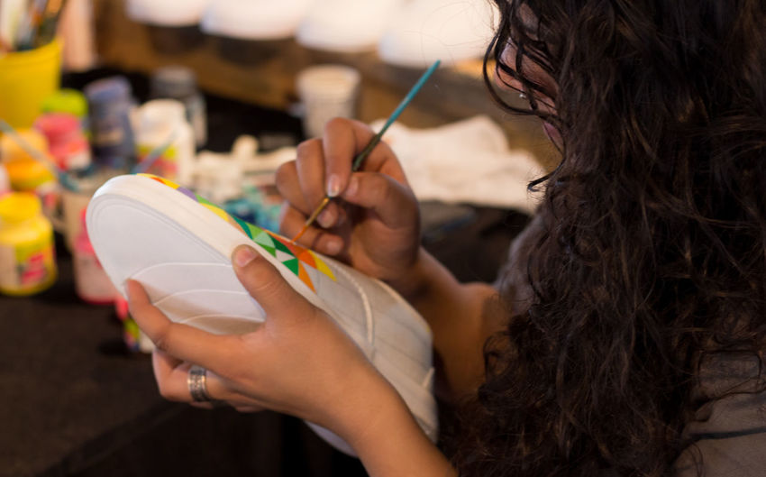 A female designer hand painting a shoe colorfully using a thin paint brush.