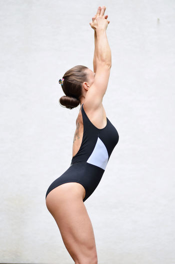 Side View Of Young Woman Practicing Yoga Against White Wall
