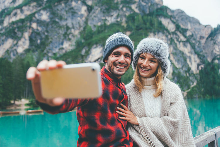 Smiling man taking selfie with girlfriend standing by lake