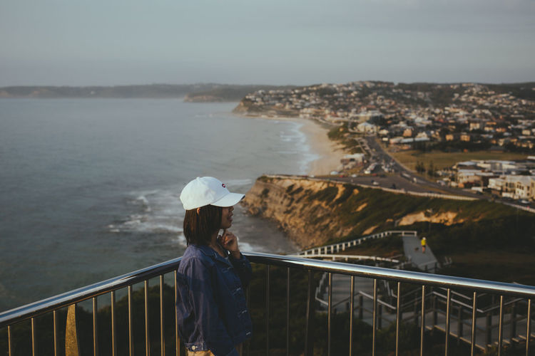 Woman standing by railing and cityscape against sea and sky