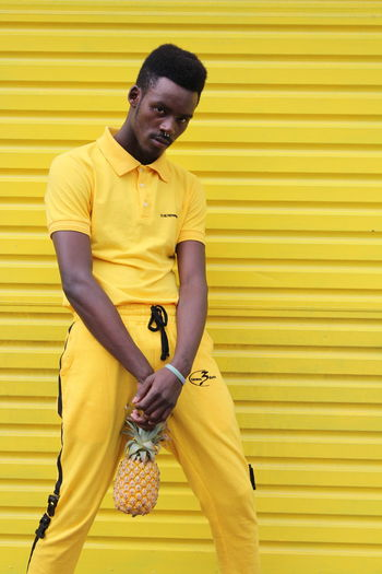 Adult Casual Clothing Day Front View Holding Leisure Activity Lifestyles Looking At Camera One Person Outdoors Portrait Real People Standing Three Quarter Length Wall - Building Feature Yellow Yellow Background Young Adult Young Men The Fashion Photographer - 2018 EyeEm Awards