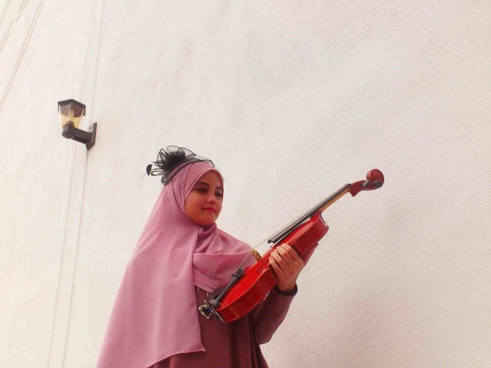 Girl holding violin while standing against wall