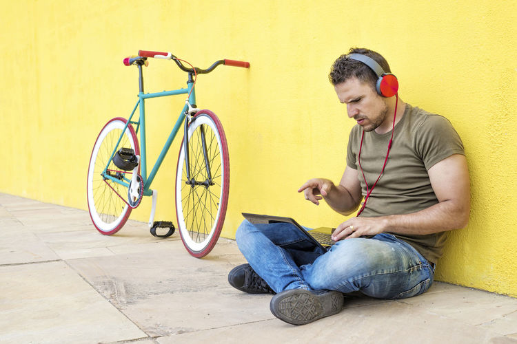 Side view of attractive guy is sitting on the floor with trendy look, writing in notebook using computer, having headphones while looking at screen against a yellow wall Casual Clothing Full Length One Person Young Adult Bicycle Young Men Sitting Indoors  Transportation Holding Adult Men Real People Mid Adult Flooring Looking Crouching Jeans Young Man Hipster Trendy Fashionable Hat T-shirt Sitting Outdoors Headphones Bike Fixie Laptop Using Laptop Vintage Yellow Side View