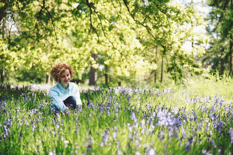 Thoughtful Smiling Woman Sitting Amidst Plants In Forest On Sunny Day
