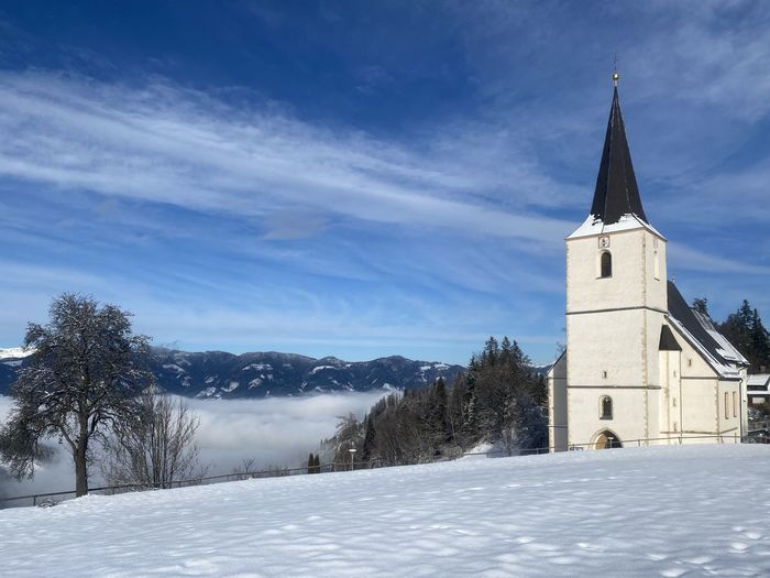 Church by building against sky during winter