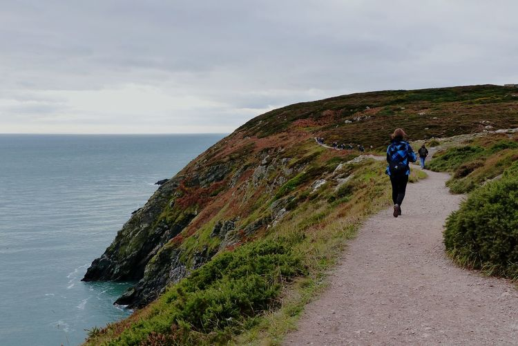 Rear view of woman walking on mountain road by sea against sky