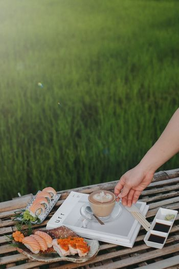 Cropped image of hand holding food on table