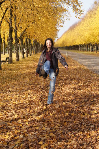 Young woman kicking autumn leaves on field by trees