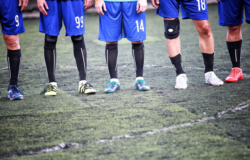 Low Section Of Soccer Players Standing On Playing Field