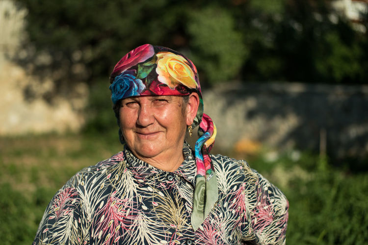 Portrait Of Senior Woman Wearing Colorful Headscarf Outdoors