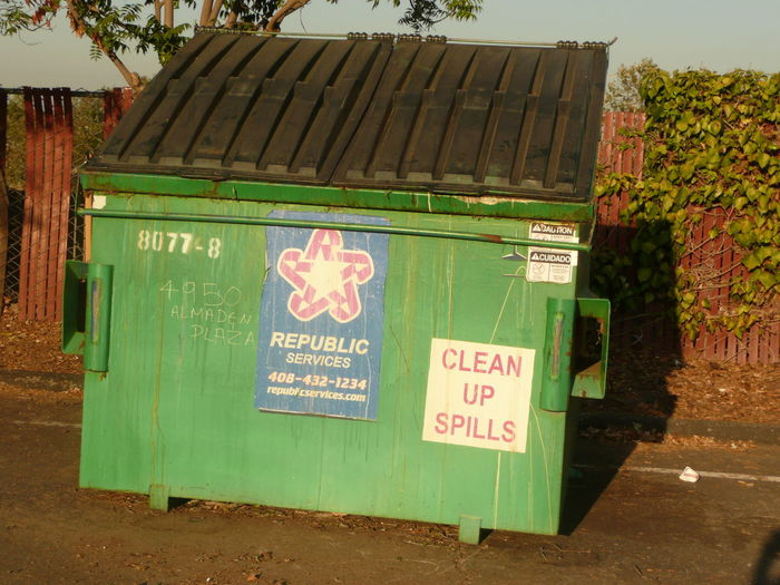 a green dumpster behind safeway Commercial Sign Communication Day Dumpster Entrance Fence Green Green Color Information Sign Ivy Neatness Non-western Script Outdoors Sign Symbol Text Trash Container Utility Waste Disposal Western Script