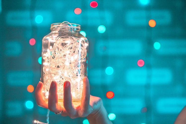 Close-up of hand holding illuminated glass