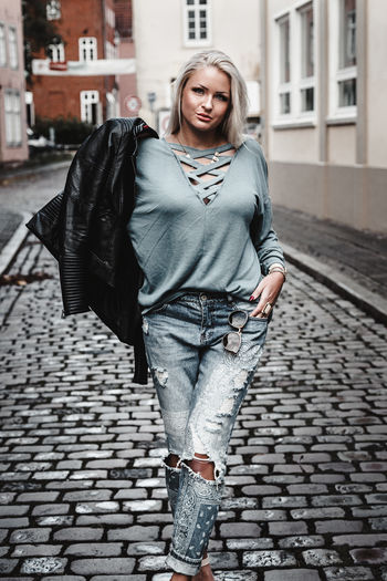Portrait Of Young Woman Standing On Cobblestone Street