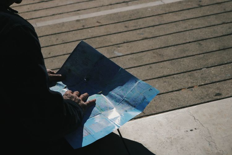 Midsection Of Man Reading Map In City During Sunny Day