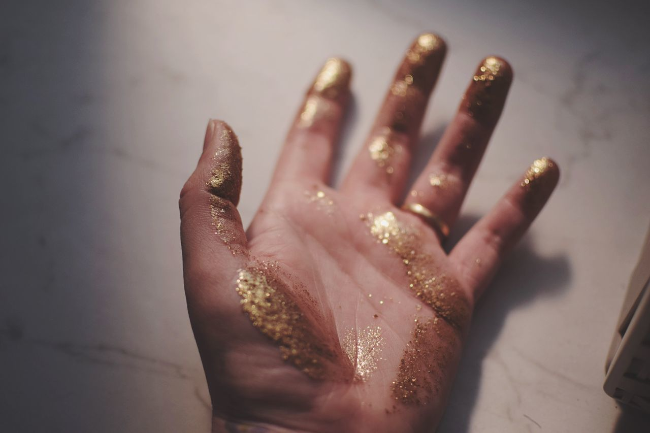 Cropped image of woman hand covered with glitter on marble