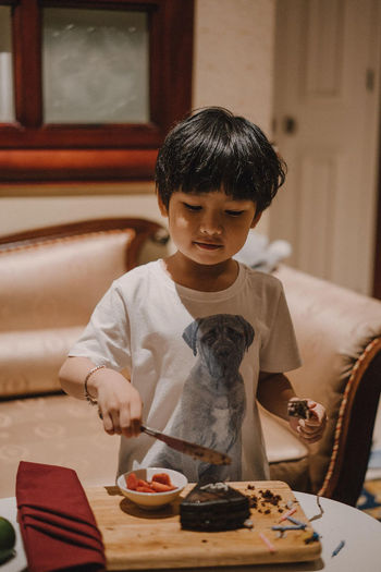 Boy holding food on table at home
