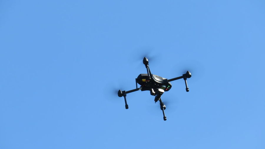 Low Angle View Of Drone Flying Against Clear Blue Sky