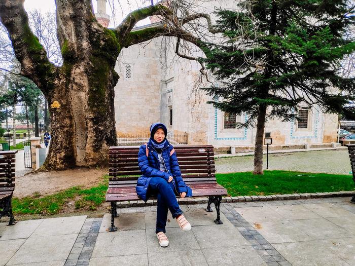 Full length portrait of teenage girl sitting on bench against building