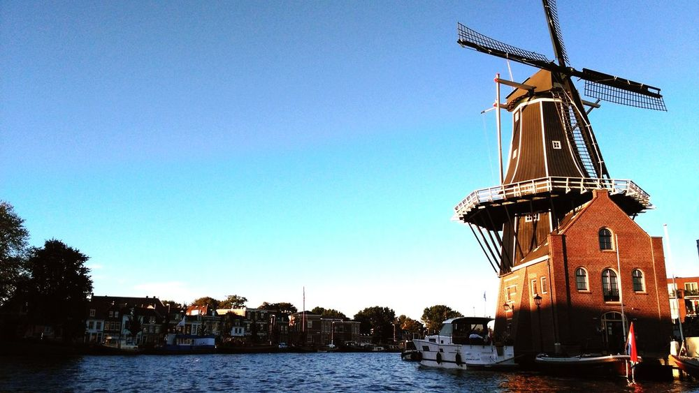 EyeEm Selects Water Nautical Vessel River Outdoors Architecture Sky Day Travel Destinations Business Finance And Industry City Building Exterior No People Blue Clear Sky Tall Ship Cityscape Urban Skyline Nature Sailing Ship Haarlem Netherlands Windmill Molen De Adriaan EyeEmNewHere