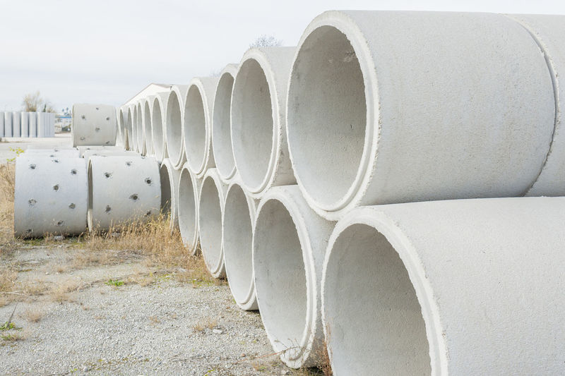 Stacked Pipes On Field Against Sky