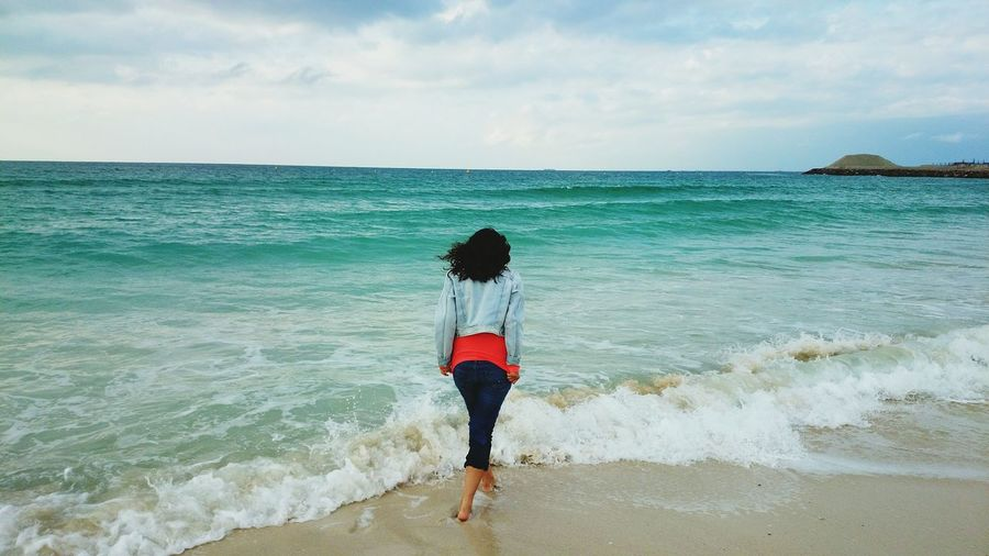Rear view of woman standing by waves on shore against sky