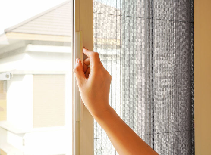 Woman hand open retractable pleated insect screen and window