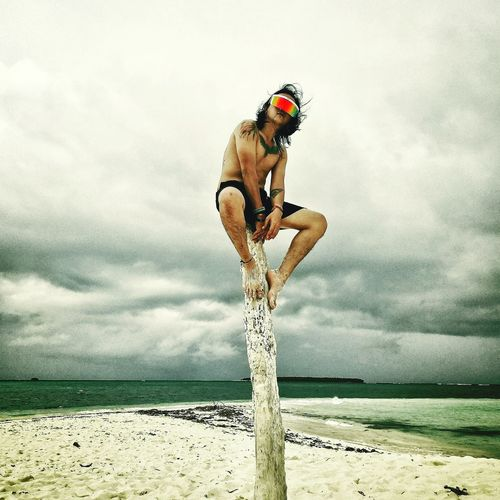 Man wearing a virtual reality headset while sitting on wood at beach against cloudy sky