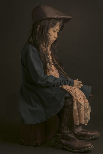 Girl sitting on suitcase against black background