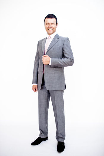 Man in classic suit on the white background. Studio shot. Classic Standing Adult Business Person Businessman Cut Out Formalwear Front View Full Frame Full Length Gray Indoors  Looking At Camera Males  Men Menswear One Person Portrait Smiling Standing Studio Shot Suit Well-dressed White Background White Backround