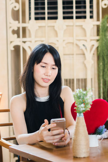 Beautiful Woman Black Hair Casual Clothing Communication Connection Front View Hair Hairstyle Holding Leisure Activity Lifestyles Mobile Phone One Person Portable Information Device Real People Smart Phone Technology Waist Up Wireless Technology Women Young Adult Young Women