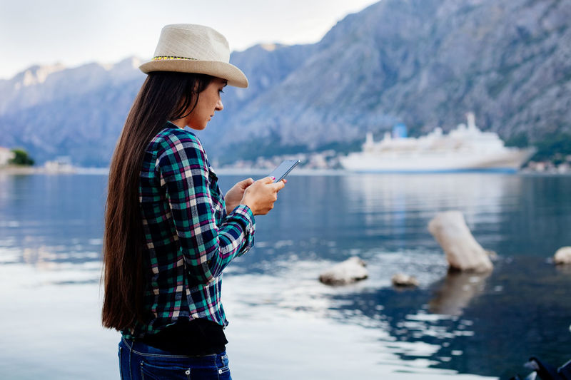 woman chatting on smart phone in picturesque location. Authentic woman in Bay on vacations with mobile phone. Adult Adults Only Authentic Bay Chatting Communication Cruise Ship EyeEm Best Shots Eyeem Travel Hat Leisure Long Hair Mobile Conversations Montenegro Mountain Nature One Person One Woman Only Outdoors Sea Smart Phone Technology Travel Photography Vacation Wireless Technology