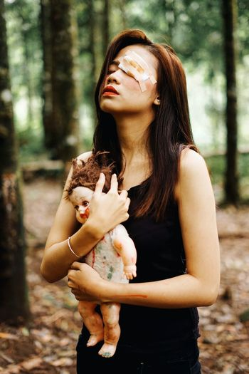 Young Woman With Wounded Eye Holding Doll While Standing In Forest