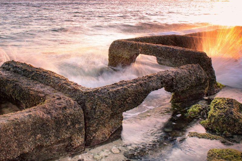 Sea waves splashing on rocks against sky during sunset