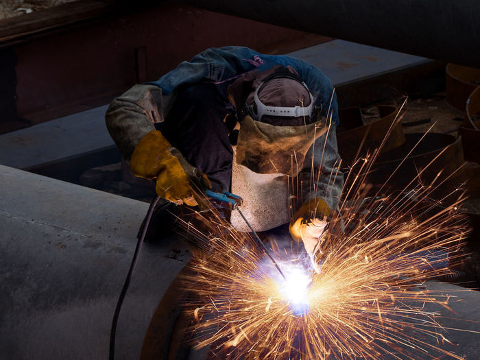 Man Working On Metal In Factory