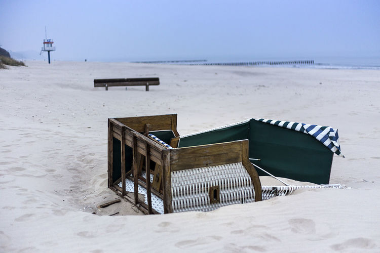 Lifeguard hut on beach against sky during winter