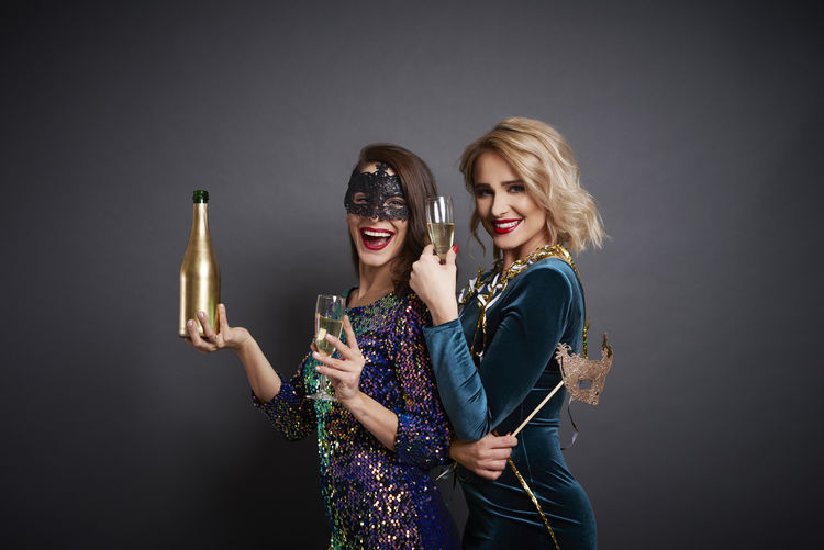 Portrait of smiling women with champagne standing against gray background