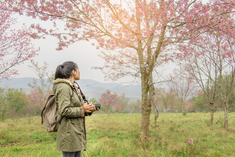 Woman Holding Camera While Hiking In Forest