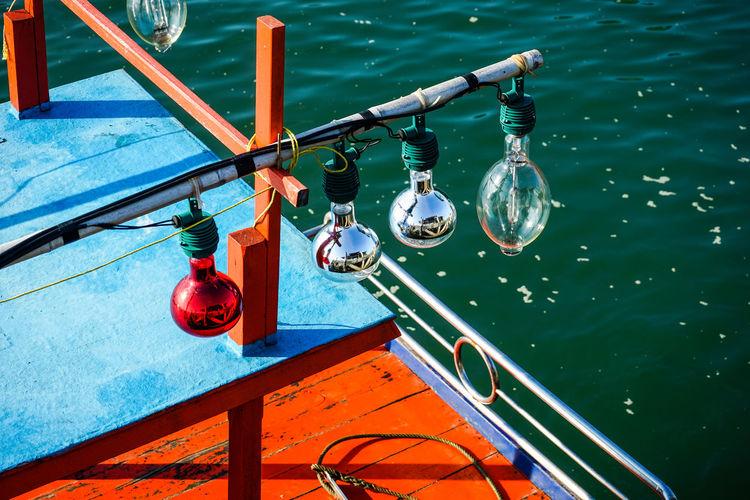 High angle view of light bulbs hanging on railing