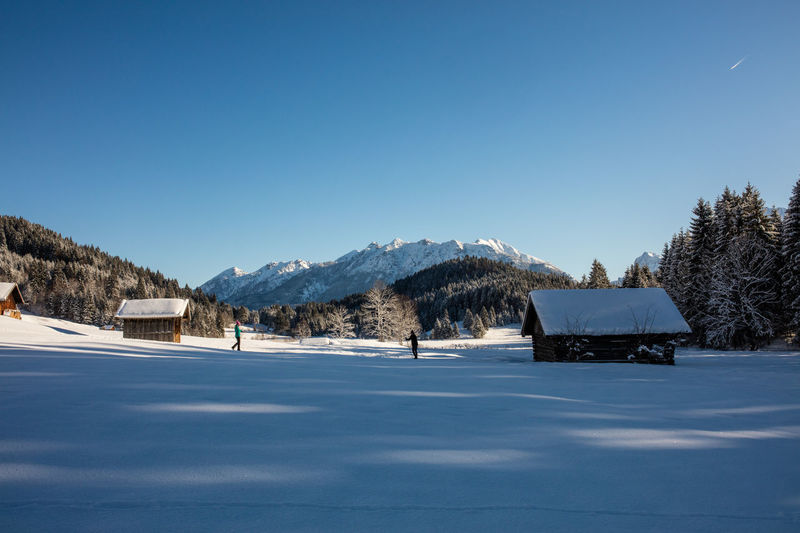 A cross-country skiing trail in the baverian alps, Germany. Bavaria Clear Sky Cross-Country Skiing Fun Trees Winter Wintertime Activity Alps Bavarian Alps Beauty In Nature Cabins  Day Daylight Langlauf Loipe Mountain Outdoors Real People Skiing Track Snow Sports Sun Trail Tranquil Scene